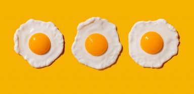 Three fried eggs on a yellow background
