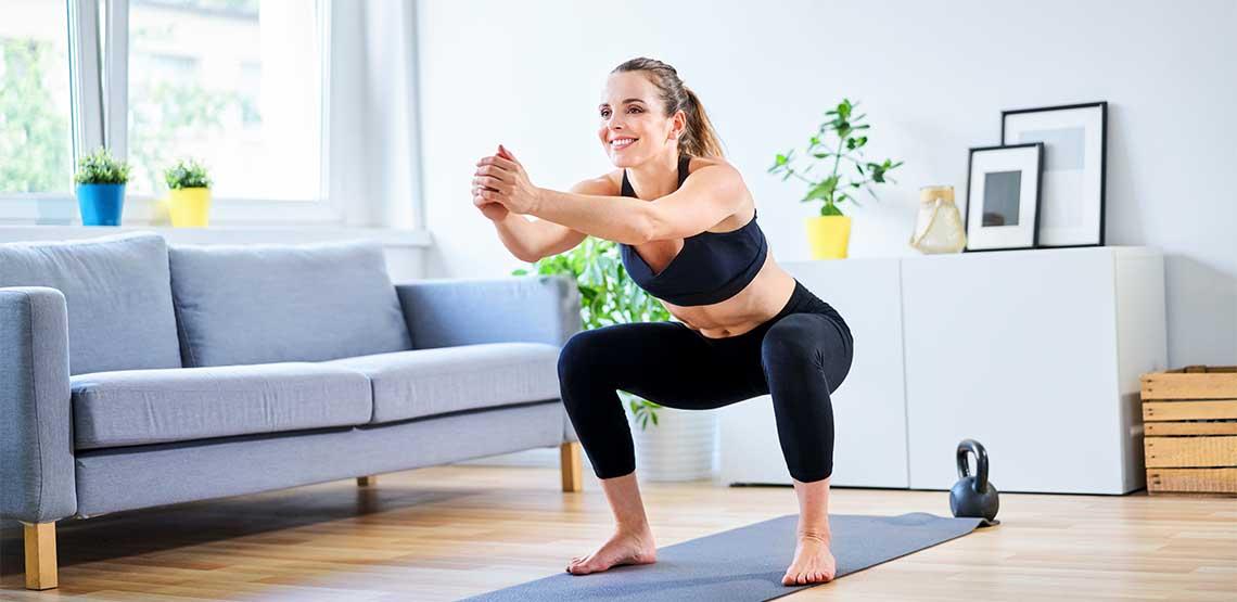 A woman squatting on a yoga mat.