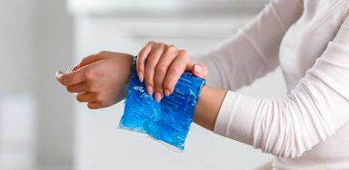 A person pressing an ice pack to their wrist.