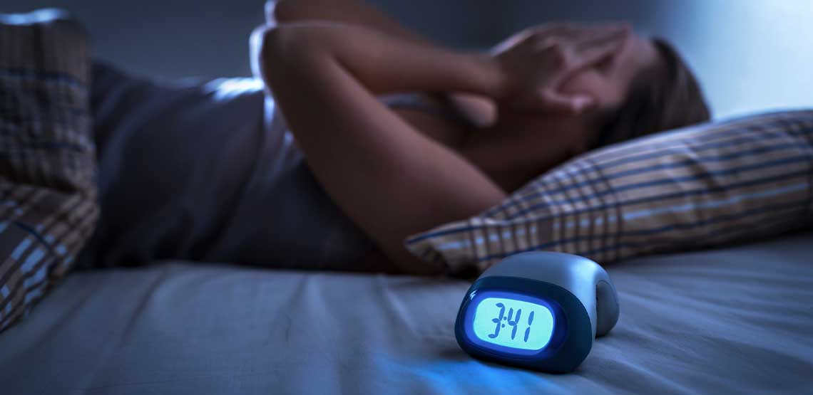 A person laying in bed at night with their hands on their face with an alarm clock next to them.