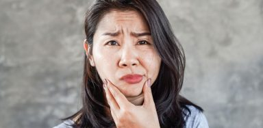 A woman making an uncomfortable face and holding her mouth.