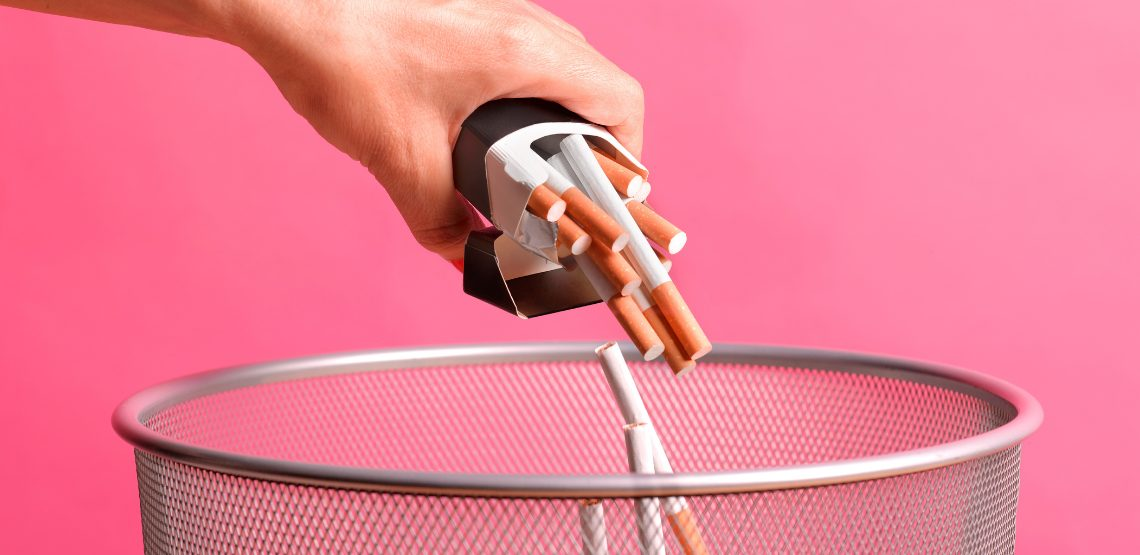 A person throwing cigarettes into a garbage can.