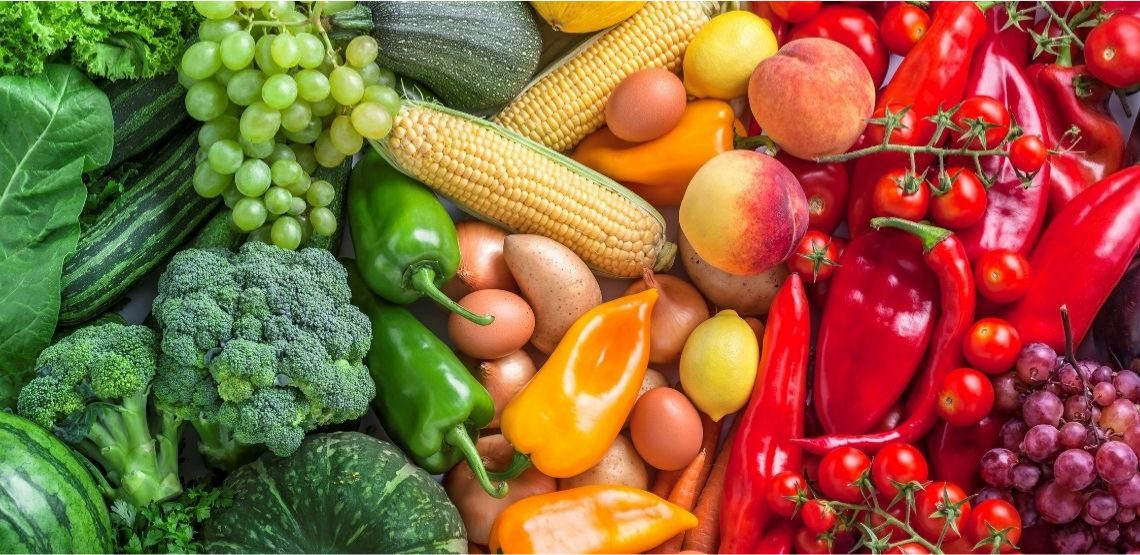 A table full of green, orange, yellow, and red vegetables.