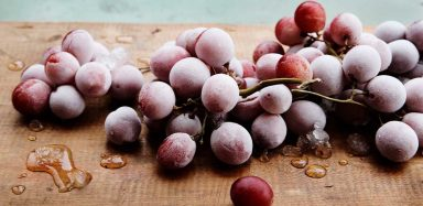 A bunch of frozen red grapes sitting on a brown cutting board.